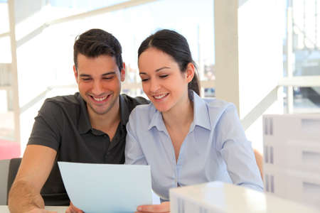 Happy young couple signing property purchase contract  photo