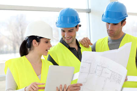 building safety: Construction workers looking at building plan
