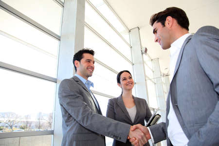 Business partners shaking hands in meeting hall photo