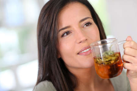 infusion: Portrait of young woman drinking herbal infusion Stock Photo