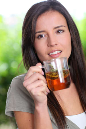woman drinking tea: Portrait of young woman drinking herbal infusion Stock Photo