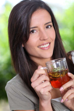 tea break: Portrait of young woman drinking herbal infusion Stock Photo