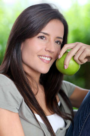 Portrait of woman sitting outside with apple photo