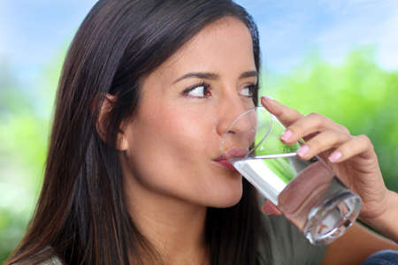 Water glass: Portrait of smiling woman holding glass of water