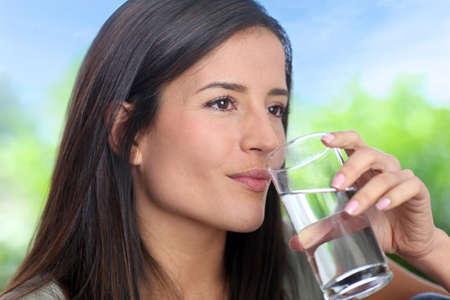 copa de agua: Retrato de la sonrisa mujer que sostiene vidrio de agua