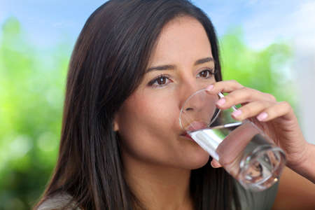 drinking glass: Portrait of smiling woman holding glass of water