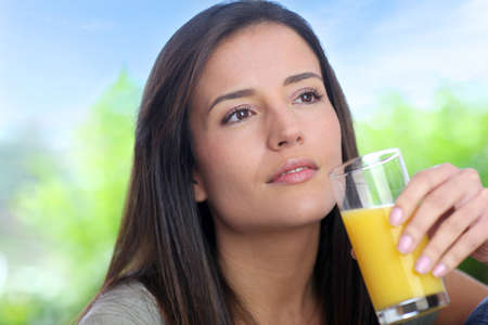 Young woman drinking fresh fruit juice photo