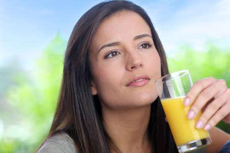 Young woman drinking fresh fruit juice photo