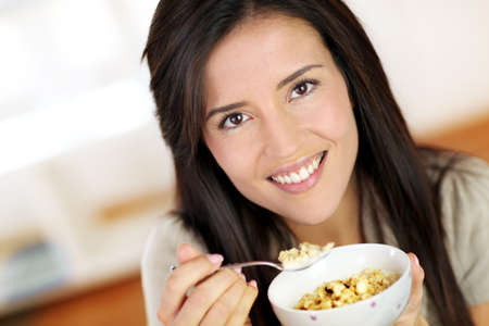 Beautiful brunette eating cereals in the morning photo