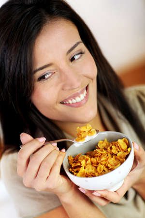 corn flakes: Cheerful woman eating corn flakes for breakfast
