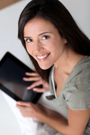 above 25: Young smiling woman using electronic tablet Stock Photo