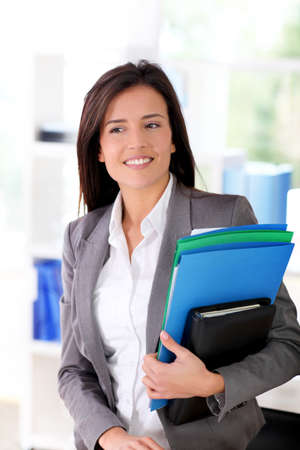 Cheerful saleswoman holding files Stock Photo - 12122027