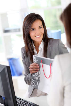 cash register: Beautiful garment store seller talking to customer