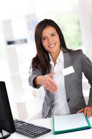 fair woman: Portrait of beautiful smiling hostess giving handshake