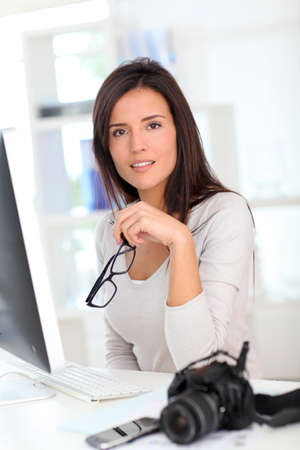 Young woman photo reporter sitting in front of desktop computer photo