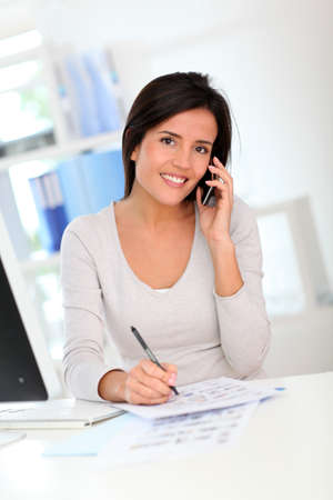 Woman designer on the phone with client Stock Photo - 12122029