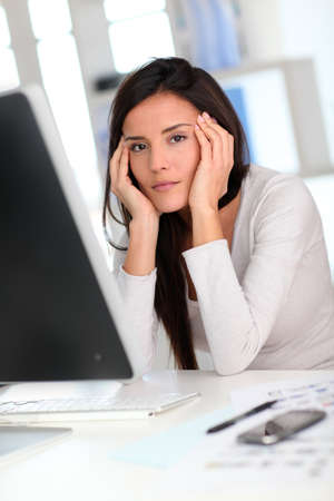 Woman in front of desktop computer having a headache photo