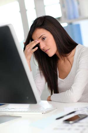 ordinateur de bureau: Femme devant ordinateur de bureau ayant un mal de t�te Banque d'images