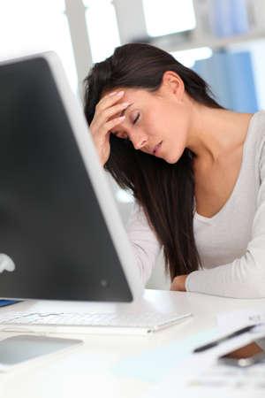 hoofdpijn: Vrouw voor desktop computer met een hoofdpijn