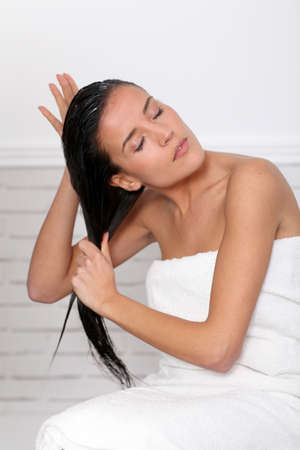 Beautiful woman applying hair conditioner photo