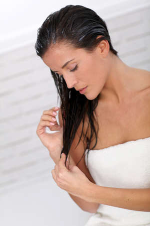 tratamiento capilar: Hermosa mujer de aplicar el acondicionador del pelo