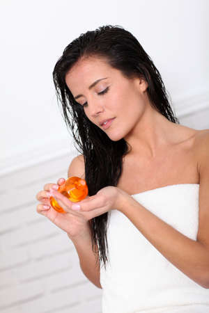 woman washing hair: Attractive young woman holding scented oil bottle