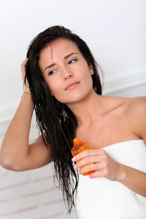 Attractive young woman holding scented oil bottle photo