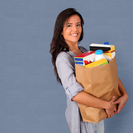 Young woman carrying bag of grocery photo