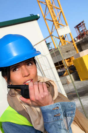 building site: Site manager using walkie-talkie on building site Stock Photo