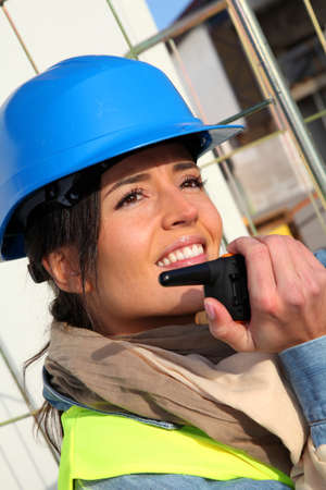Site manager using walkie-talkie on building site Stock Photo
