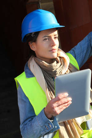 building site: Architect on building site using electronic tablet