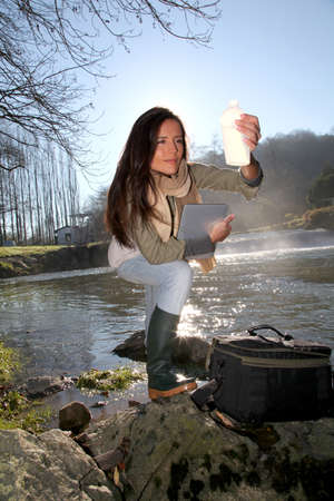water quality: Woman testing quality of natural water