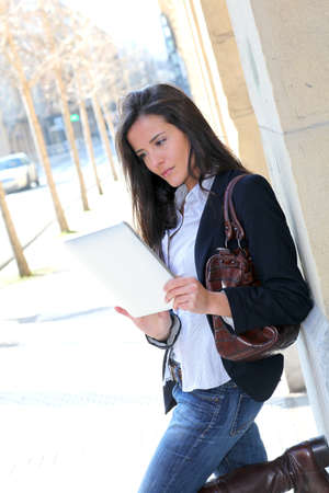 Woman leaning on wall in town with electronic tablet photo