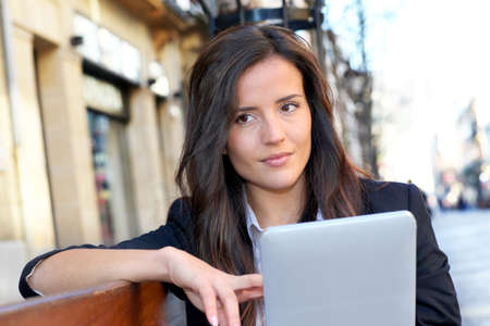Woman sitting on public bench with tablet photo