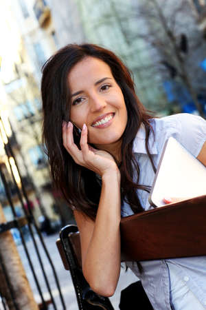 Young woman sitting on public bench with mobile phone photo