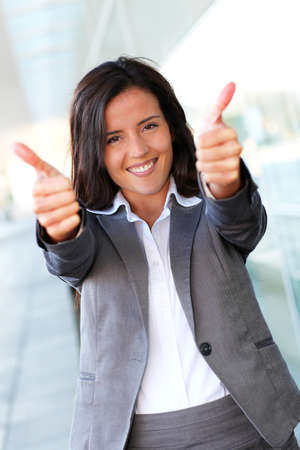 Cheerful businesswoman showing tumbs up photo