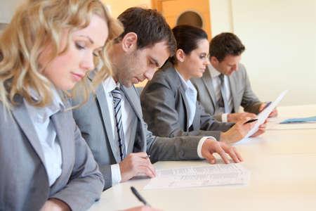 신청서에 서명하는 젊은 비즈니스 사람들이 스톡 콘텐츠