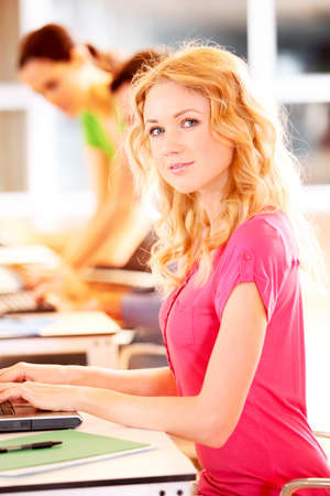 Beautiful blond girl working on laptop computer photo