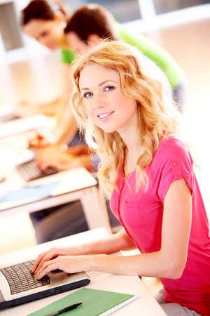 Beautiful blond girl working on laptop computer Stock Photo - 12557118
