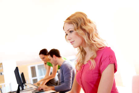 Beautiful blond girl working on laptop computer Stock Photo - 12556643