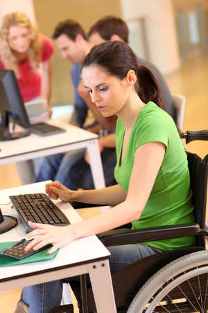 adult learning: Young woman in wheelchair working in office