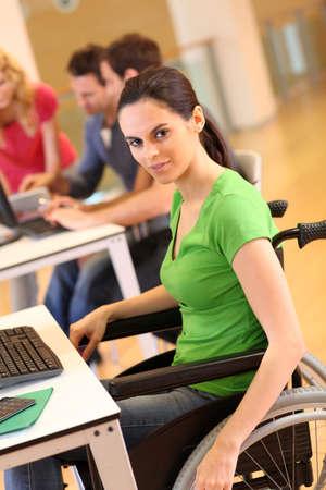 handicap people: Mujer joven en silla de ruedas de trabajo en la oficina Foto de archivo