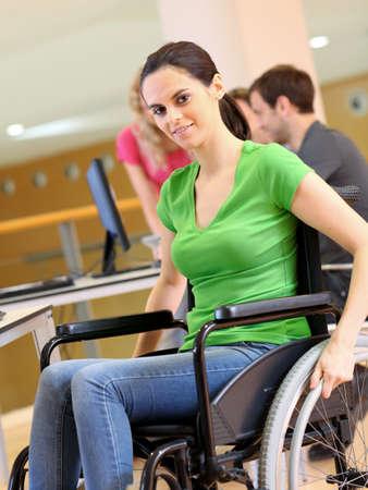 persona en silla de ruedas: Mujer joven en silla de ruedas de trabajo en la oficina Foto de archivo
