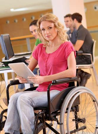 handicap: Giovane donna in sedia a rotelle di lavoro in ufficio