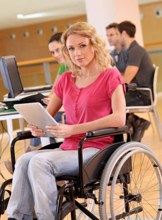 Young woman in wheelchair working in office photo