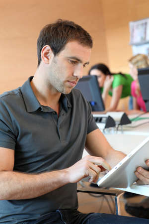 electronic tablet: Young man using tablet in office