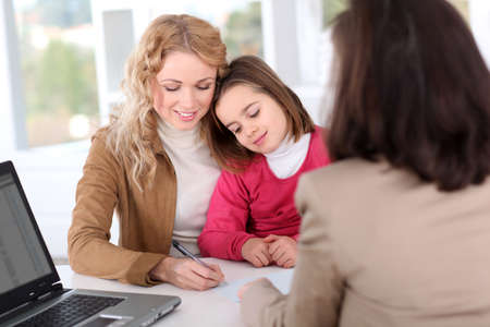 Woman in real-estate agency with kid photo