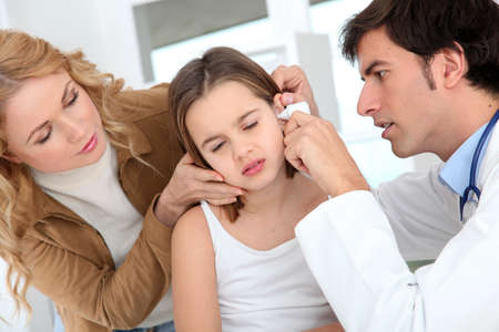Doctor looking at little girl ear infection Stock Photo - 12556996