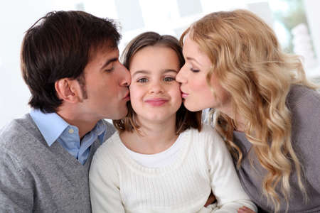 Portrait of parents kissing their daughter photo