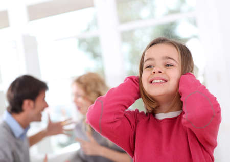 Child hiding her ears from parents fight photo